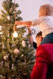 Giovane famiglia felice che si agghinda l'albero di Natale Vista posteriore fotografie stock