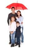 Giovane famiglia felice che si leva in piedi sotto un ombrello Fotografia Stock Libera da Diritti