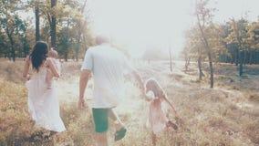 Giovane famiglia felice che spende insieme tempo fuori in natura verde archivi video