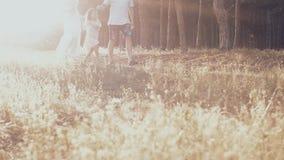 Giovane famiglia felice che spende insieme tempo fuori in natura verde video d archivio