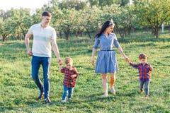 Giovane famiglia felice che spende insieme tempo fuori in natura verde Genitori che giocano con i gemelli fuori Immagine Stock Libera da Diritti