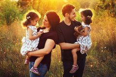 Giovane famiglia felice con due bambini all'aperto Gemella le ragazze Fotografia Stock