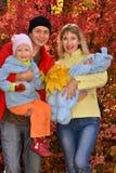 Giovane famiglia felice con i bambini nel parco di autunno fotografia stock libera da diritti