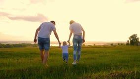 Giovane famiglia felice con il bambino Vanno al campo verde pittoresco al tramonto Il ragazzo è alzato dei genitori Tramonto stock footage
