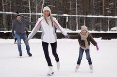 Giovane famiglia felice con il pattino del bambino alla pista di pattinaggio sul ghiaccio all'aperto nell'inverno Bella famiglia  fotografia stock libera da diritti