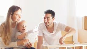 Giovane famiglia felice con istruzione della lettura del ragazzino e montare insieme mobilia al salone stock footage