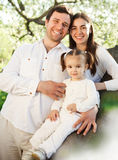 Giovane famiglia felice con la neonata all'aperto Fotografia Stock