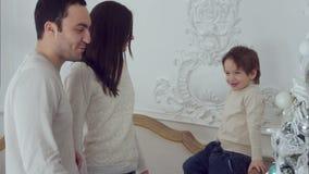 Giovane famiglia felice e piccola riunione del figlio intorno all'albero di Natale video d archivio
