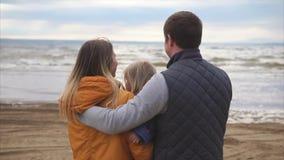 Giovane famiglia felice L'uomo con la donna e la bambina che sta sull'oceano puntellano video d archivio
