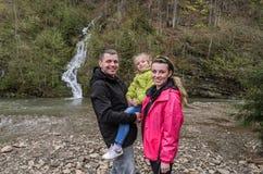 Giovane famiglia felice: mamma, pap? e figlia sui precedenti di una cascata della montagna immagine stock libera da diritti