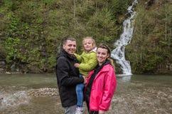 Giovane famiglia felice: mamma, pap? e figlia sui precedenti di una cascata della montagna fotografie stock libere da diritti