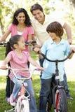 Giovane famiglia ispana che cicla nel parco fotografie stock