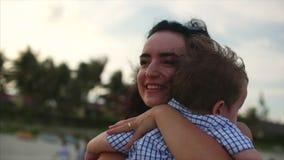 Giovane famiglia, madre che abbraccia suo figlio sulla famiglia felice della costa, lungo il litorale video d archivio