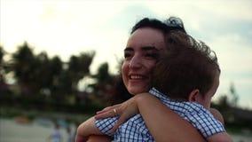 Giovane famiglia, madre che abbraccia suo figlio sulla famiglia felice della costa, lungo il litorale archivi video