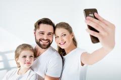 Giovane famiglia in magliette bianche che prendono selfie con lo smartphone in studio fotografia stock