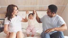 Giovane famiglia multi-etnica che gioca a letto video d archivio