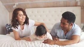 Giovane famiglia multi-etnica che gioca a letto archivi video