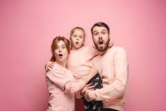 Giovane famiglia sorpresa che esamina macchina fotografica sul rosa immagine stock