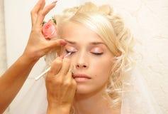 Giovane fare della sposa compone immagine stock
