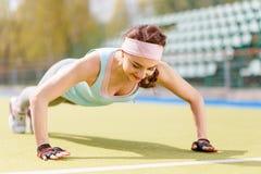 Giovane fare sportivo della donna spinge verso l'alto l'esercizio all'aperto Immagini Stock Libere da Diritti