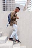 Giovane felice che cammina giù le scale con la borsa ed il telefono cellulare Fotografie Stock Libere da Diritti