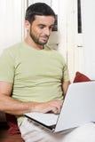 Giovane felice che lavora al computer portatile a casa Immagini Stock Libere da Diritti