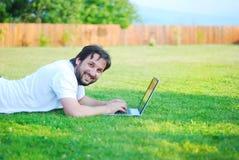 Giovane felice che lavora al computer portatile nel bello gre Immagini Stock