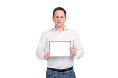 Giovane felice che mostra lo schermo di computer in bianco della compressa sopra fondo bianco esaminando macchina fotografica Fotografia Stock