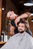 giovane felice che ottiene taglio di capelli dal barbiere professionista fotografia stock