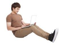 Giovane felice che per mezzo del computer portatile Fotografie Stock Libere da Diritti