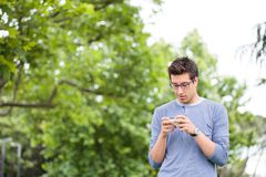 Giovane felice che per mezzo dello Smart Phone Immagine Stock