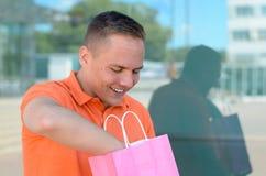 Giovane felice che ricerca in un sacchetto della spesa Immagini Stock Libere da Diritti