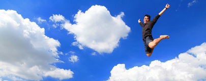 Giovane felice che salta con la priorità bassa del cielo Fotografie Stock Libere da Diritti