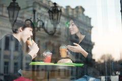 Giovane felice che si siede in caffè con sua sorella Immagini Stock