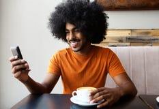 Giovane felice che si siede con la tazza di caffè ed il telefono cellulare Immagine Stock Libera da Diritti