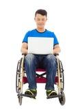 Giovane felice che si siede su una sedia a rotelle con un computer portatile Immagine Stock