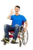 Giovane felice che si siede su una sedia a rotelle e su un gesto giusto Fotografia Stock Libera da Diritti