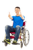 Giovane felice che si siede su una sedia a rotelle e su un pollice su Fotografie Stock Libere da Diritti