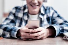 Giovane felice che sorride e che ritiene soddisfatto con il suo dispositivo moderno immagine stock libera da diritti