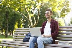 Giovane felice con il computer portatile all'aperto Immagini Stock