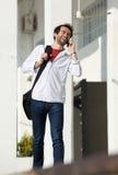 Giovane felice con la borsa che chiama dal telefono cellulare all'aperto Immagine Stock