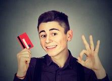 Giovane felice con la carta di credito che mostra segno giusto Fotografia Stock