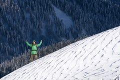 Giovane felice con lo zaino che sta sul pendio di montagna nevoso Viandante della montagna o dell'alpinista Fotografie Stock