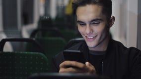 Giovane felice facendo uso dello smartphone mentre tram di guida, steadicam sparato Movimento lento stock footage
