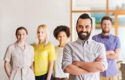 Giovane felice sopra il gruppo creativo in ufficio Immagine Stock Libera da Diritti