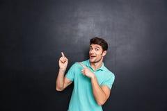 Giovane felice sorridente che indica le dita via con entrambe le mani Fotografie Stock Libere da Diritti