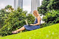 Giovane femmina astuta dello studente in abbigliamento casual Donna che si siede sulla terra dell'erba, lavorante al computer del Fotografie Stock