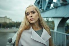Giovane femmina bionda alla moda in cappotto sulla via fotografia stock