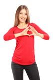 Giovane femmina casuale con le sue mani sotto forma di cuore Immagini Stock Libere da Diritti