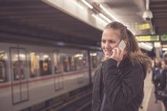 Giovane femmina che fa una chiamata con lo smartphone alla stazione della metropolitana Fotografia Stock